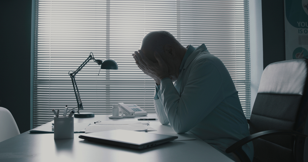man at office desk stressed out